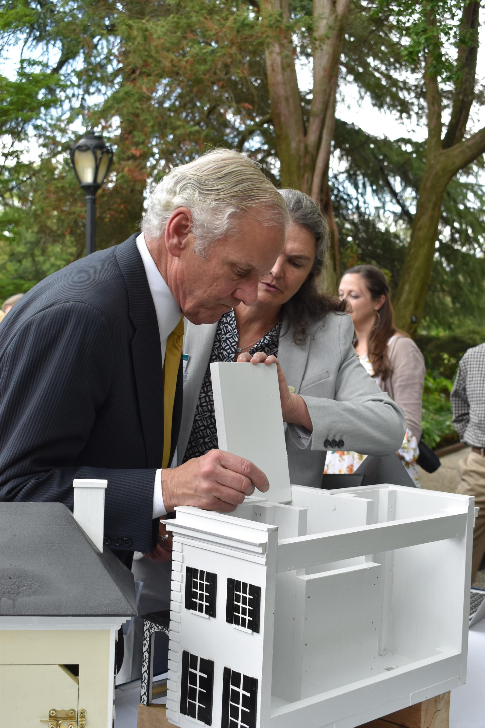 Sharon Richardson shows Gov. McMaster the handcrafted, mansion replica birdhouses
