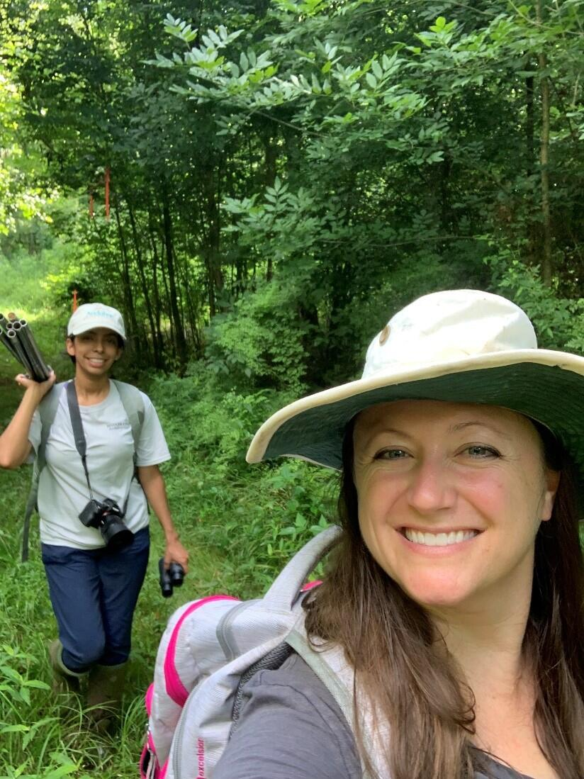 Two women are walking in dense forest edge with optical equipment and backpacks taking a selfie