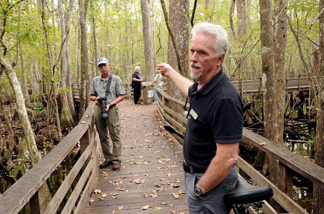 Mike Dawson answers questions from visitors on the boardwalk Saturday, Oct. 20 at Beidler Forest.